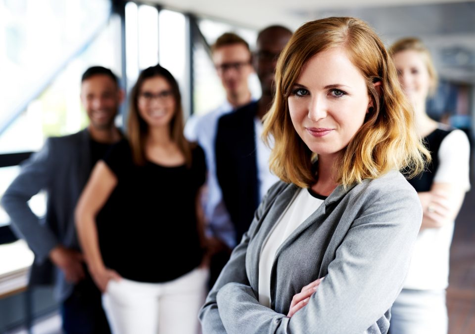 Young white female executive with arms crossed standing in front of colleagues grinning at camera